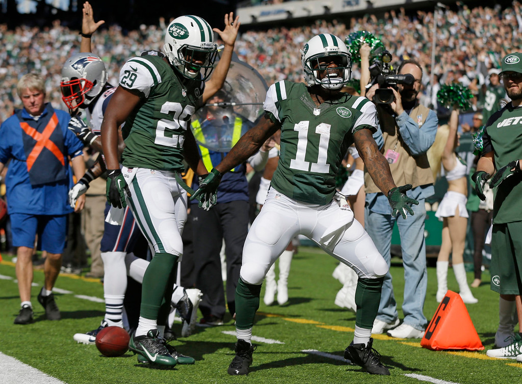 . New York Jets wide receiver Jeremy Kerley (11) and Bilal Powell (29) celebrate a touchdown by Kerley during the first half of an NFL football game against the New England Patriots Sunday, Oct. 20, 2013 in East Rutherford.  (AP Photo/Seth Wenig)