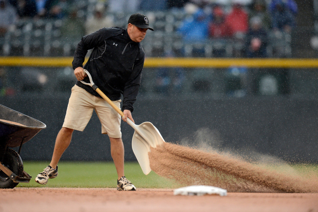 . Asst. Groundskeeper  Jason Garner throws down a premium field conditioner to dry out the wet spots on the infield during the Colorado Rockies New York Yankees game May 9, 2013 at Coors Field. (Photo By John Leyba/The Denver Post)