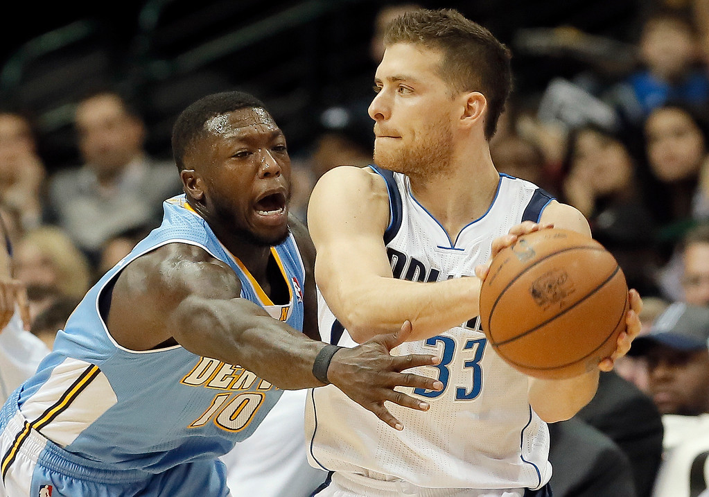 . Dallas Mavericks guard Gal Mekel (33) looks for an open teammate as Denver Nuggets Nate Robinson (10) defends during the first half of an NBA basketball game Monday, Nov. 25, 2013, in Dallas. (AP Photo/Brandon Wade)