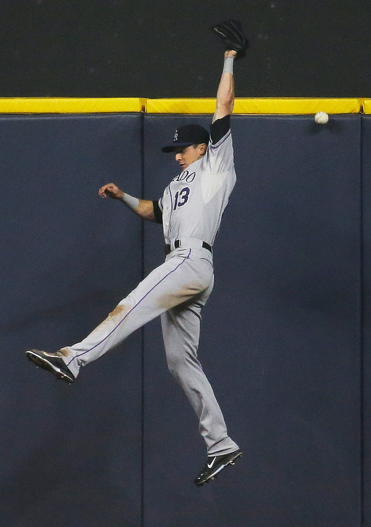 . Colorado Rockies center fielder Drew Stubbs can\'t catch a single by Milwaukee Brewers\' Jonathan Lucroy during the fifth inning of a baseball game Thursday, June 26, 2014, in Milwaukee. (AP Photo/Morry Gash)