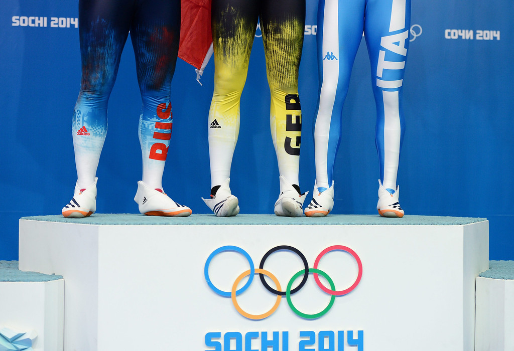 . The legs of gold medal winner Felix Loch (C) of Germany, second placed Albert Demchenko (L) of Russia and third placed Armin Zoeggeler (R) of Italy during the flower ceremony after the men\'s singles Luge at the Sanki Sliding Center at the Sochi 2014 Olympic Games, Krasnaya Polyana, Russia, 09 February 2014.  EPA/VASSIL DONEV