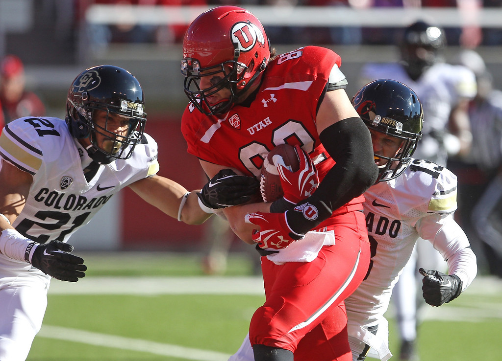 . Utah tight end Jake Murphy (82) carries the ball for a touchdown as Colorado defensive back Jered Bell (21) and teammate defensive back Parker Orms (13) defend in the first quarter during an NCAA college football game Saturday, Nov. 30, 2013, in Salt Lake City. (AP Photo/Rick Bowmer)