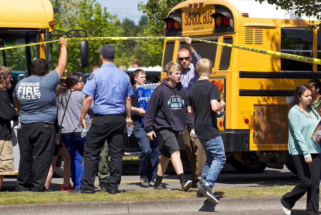 . Students arrive by bus at the Fred Meyer grocery store parking lot in Wood Village, Ore., after a shooting at Reynolds High School Tuesday, June 10, 2014, in nearby Troutdale. A gunman killed a student at the high school east of Portland Tuesday and the shooter is also dead, police said. (AP Photo/The Oregonian, Thomas Boyd)