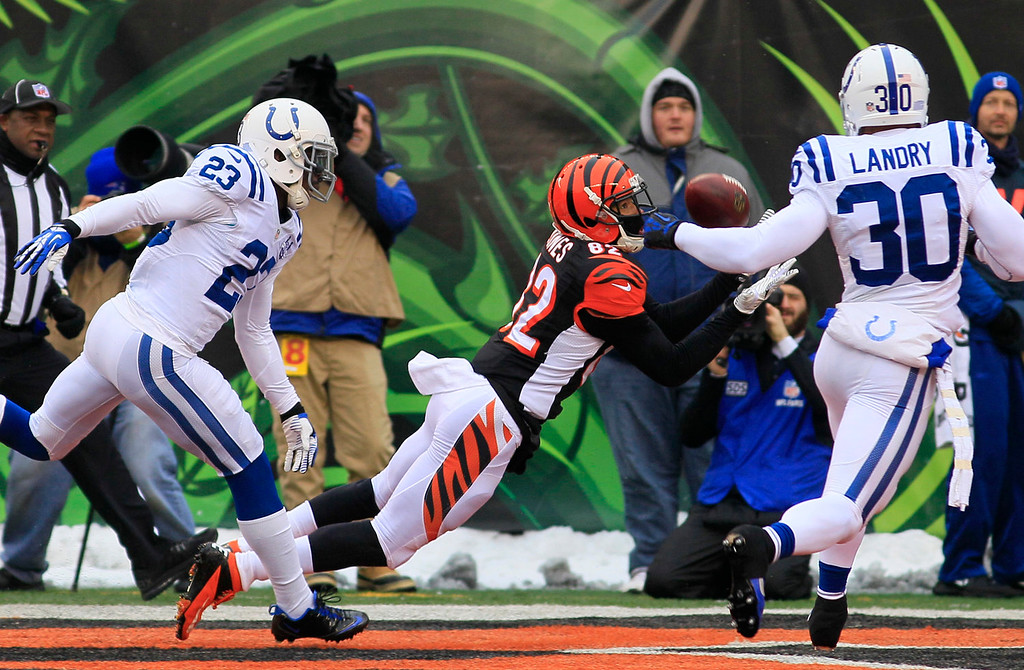 . Cincinnati Bengals wide receiver Marvin Jones (82) catches a 29-yard touchdown pass against Indianapolis Colts cornerback Vontae Davis (23) and strong safety LaRon Landry (30) in the first half of an NFL football game, Sunday, Dec. 8, 2013, in Cincinnati. (AP Photo/Tom Uhlman)