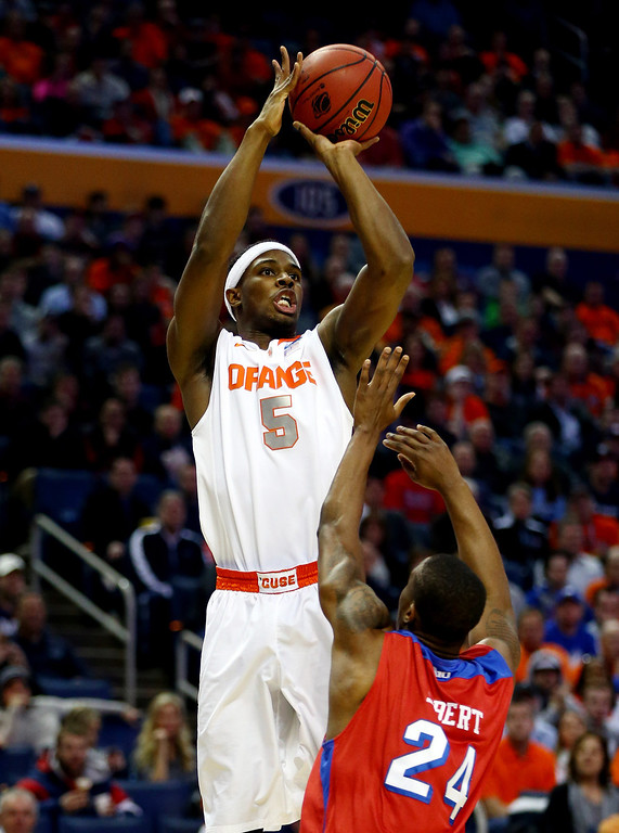 . BUFFALO, NY - MARCH 22: C.J. Fair #5 of the Syracuse Orange takes a shot over Jordan Sibert #24 of the Dayton Flyers during the third round of the 2014 NCAA Men\'s Basketball Tournament at the First Niagara Center on March 22, 2014 in Buffalo, New York.  (Photo by Elsa/Getty Images)