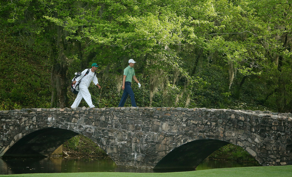 . Jordan Spieth of the United States walks with his caddie Michael Greller on the Nelson Bridge during the final round of the 2014 Masters Tournament at Augusta National Golf Club on April 13, 2014 in Augusta, Georgia.  (Photo by Andrew Redington/Getty Images)