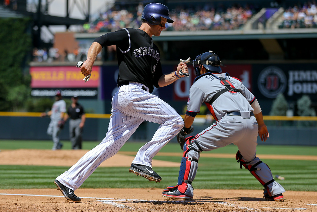 . Justin Morneau #33 of the Colorado Rockies scores a run as catcher Kurt Suzuki #8 of the Minnesota Twins waits for the throw during the first inning at Coors Field on July 13, 2014 in Denver, Colorado. (Photo by Justin Edmonds/Getty Images)