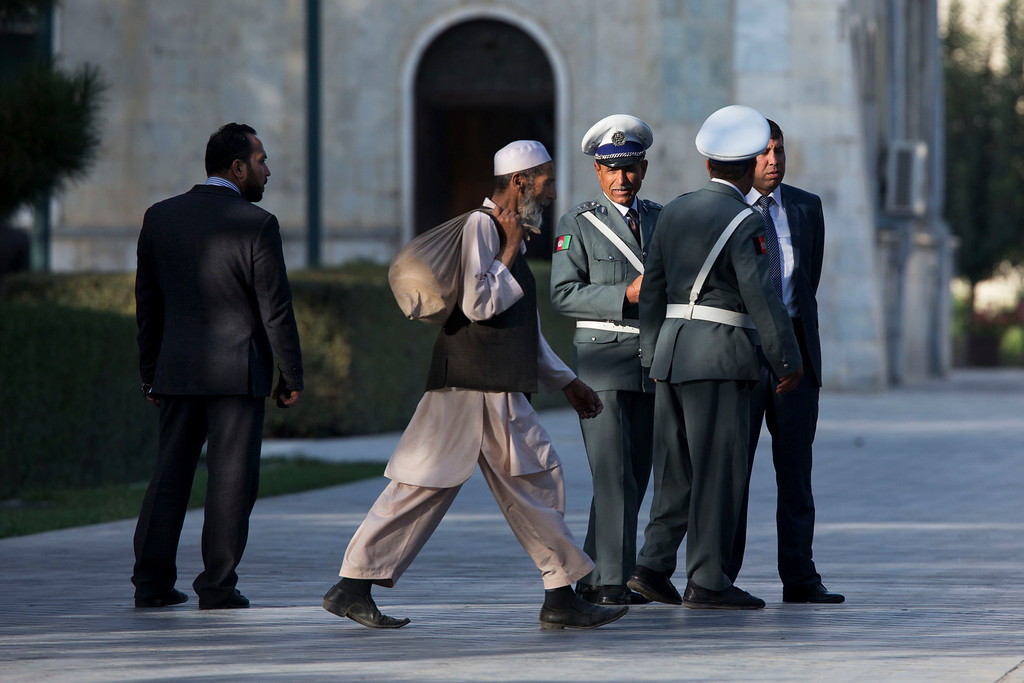 . A worker walks past Afghan guards as they wait for a news conference that has been delayed between U.S. Secretary of State John Kerry and Afghan President Hamid Karzai at the presidential palace on the second day of an unannounced stop in Kabul, Afghanistan, on Saturday, Oct. 12, 2013. Kerry extended talks Saturday with Karzai on a bilateral security agreement with the United States, and while work remains to be done a deal could be struck by the end of the day, a presidential spokesman said.  (AP Photo/Jacquelyn Martin, Pool)