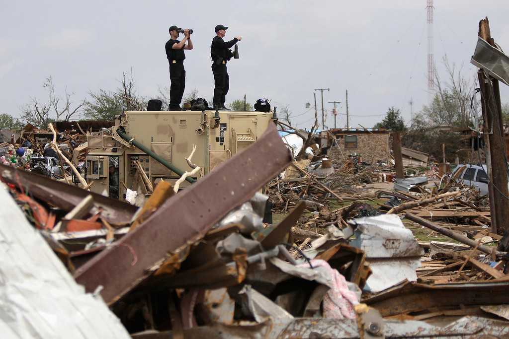 . Secret Service agents scan the rubble as U.S. President Barack Obama (not pictured) tours tornado damage in Moore, Oklahoma, May 26, 2013. Obama arrived in Moore on Sunday to tour the town that was hammered last week by a powerful tornado that killed 24 people and assure its residents that the federal government would provide long-term help.  REUTERS/Jonathan Ernst