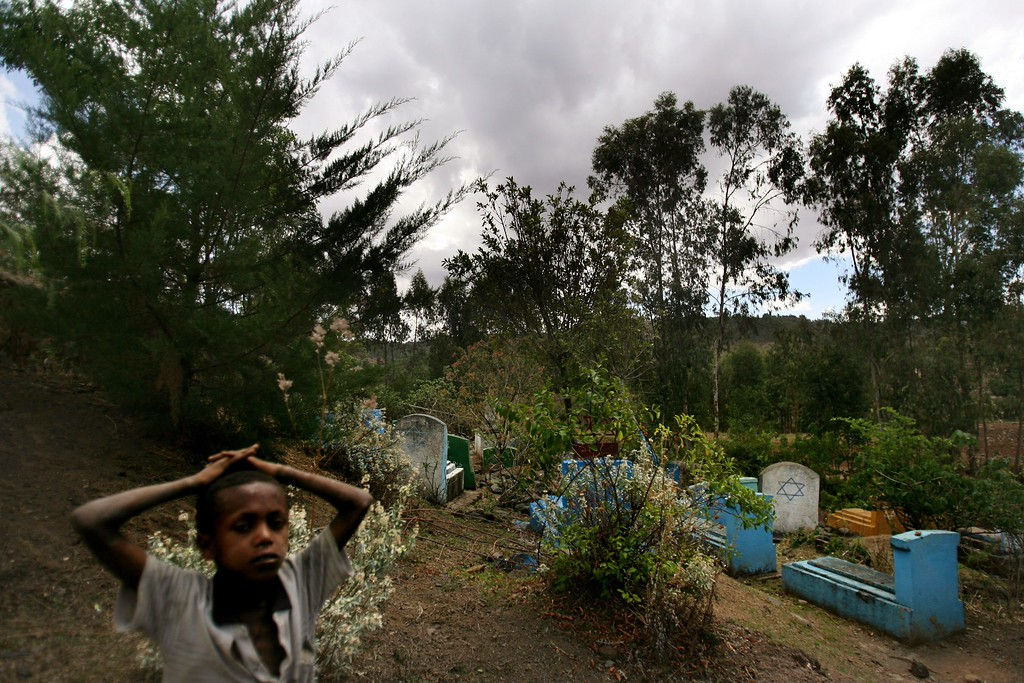 . WALLAKA, ETHIOPIA - APRIL 29: An Ethiopian boy walks through the old Jewish cemetery in this once-Jewish village that has been taken over by Christians since its original inhabitants moved to Israel, on April 29, 2007 in Wallaka in the Gondar province in northern Ethiopia. Some 2,500 Ethiopians of Jewish origins from this province remain in the East African country as Israel slowly brings them over, a few dozen at a time, on commercial flights. Since 1984, more than 73,000 Ethiopian Jews have been settled in Israel. (Photo by Uriel Sinai/Getty Images)