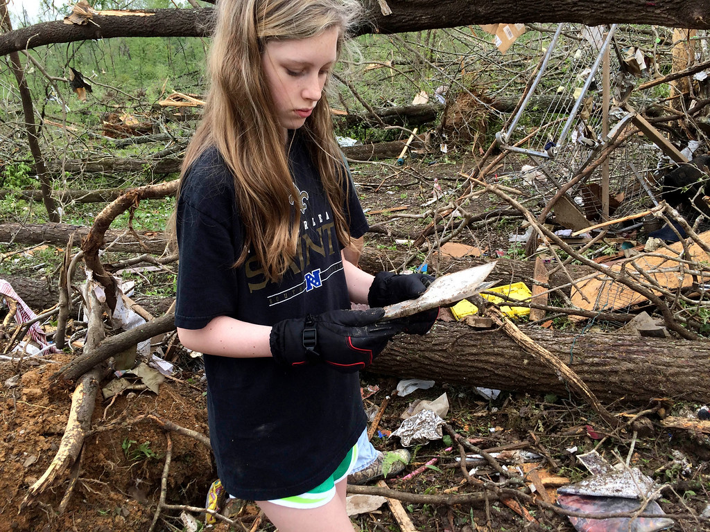 . Leah, daughter of Jon Zieske, looks for belongings at her father\'s house in Paron, Ark., Monday, April 28, 2014 after a tornado. A storm system ripped through several states in the central U.S. and left more than a dozen dead in a violent start to this year\'s storm season, officials said. (AP Photo/Christina Huynh)
