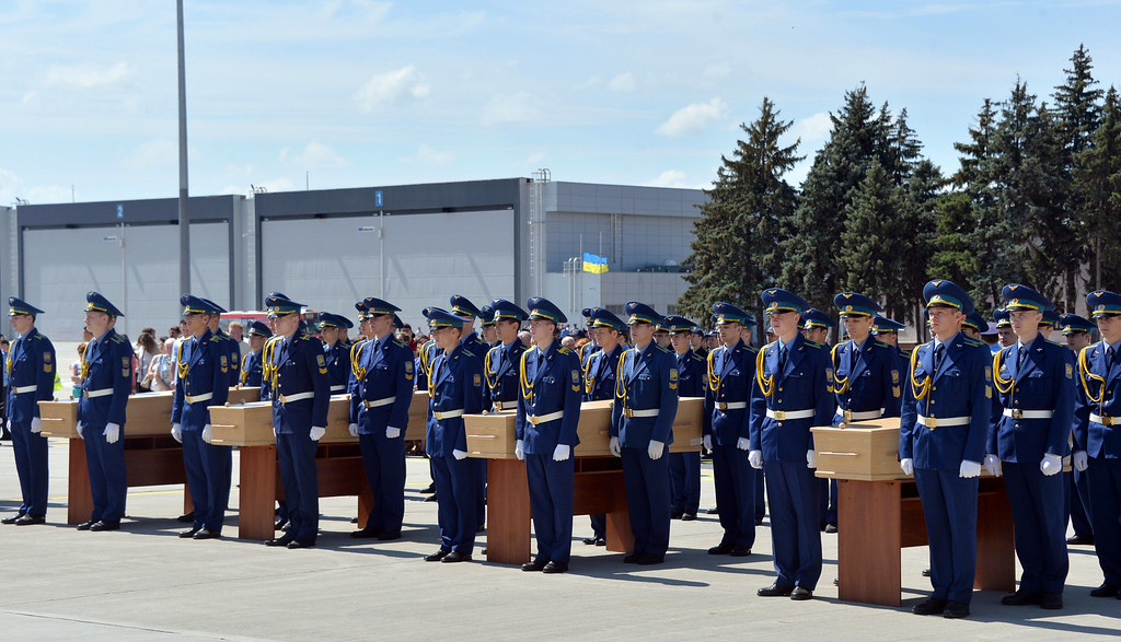 . Ukrainian soldiers carry coffins with the remains of a victims of the Malaysia Airlines flight MH17 crash during a ceremony at the airport of Kharkiv, Ukraine, on July 23, 2014. The first plane carrying bodies from downed Malaysia Airlines flight MH17 left eastern Ukraine for the Netherlands on July 23 following a sombre ceremony. The Dutch military aircraft took off from the airport in the government-controlled city of Kharkiv bound for Eindhoven after the first group of victims\' remains were loaded onto the plane in wooden coffins.   AFP PHOTO/ GENYA  SAVILOV/AFP/Getty Images