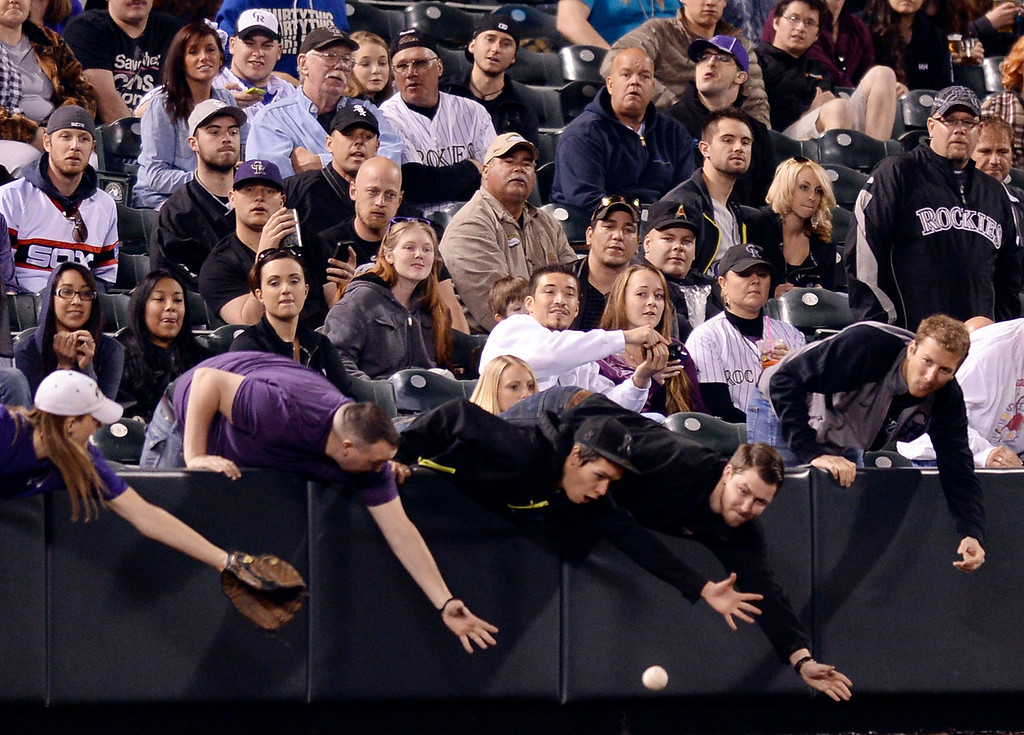 . Rockies fans reached for a foul ball in the eighth inning. The Colorado Rockies hosted the Chicago White Sox Tuesday night, April 8, 2014 at Coors Field in Denver.  (Photo by Karl Gehring/The Denver Post)