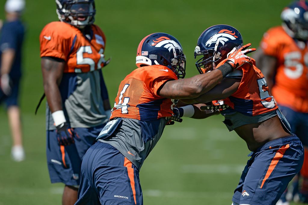 . Denver Broncos linebacker Brandon Marshall (54) and Denver Broncos linebacker Steven Johnson (53) run through blocking   drills at the Denver Broncos 2014 training camp August 11, 2014 at Dove Valley. (Photo by John Leyba/The Denver Post)