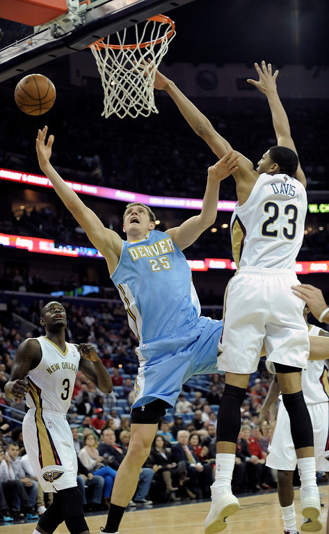 . Denver Nuggets center Timofey Mozgov (25) shoots around New Orleans Pelicans center Anthony Davis (23) during the first half of an NBA basketball game in New Orleans, Friday, Dec. 27, 2013.  (AP Photo/ Stacy Revere)