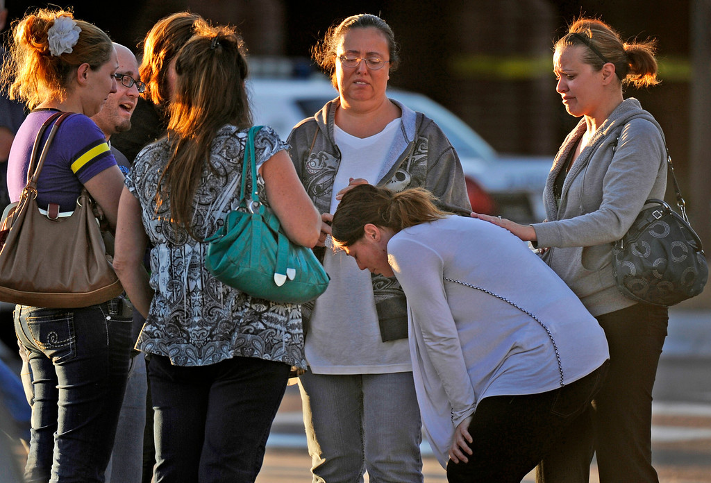 . A group of friends are overcome with emotion as they gather outside Gateway High School, Friday July 20, 2012, in Aurora. They got news that their friend was killed during a shooting, where about 50 people were shot 12 fatally early Friday inside an Aurora movie theater during a premiere showing of the new Batman movie, were taken to the high school by bus to be questioned by police. RJ Sangosti, The Denver Post