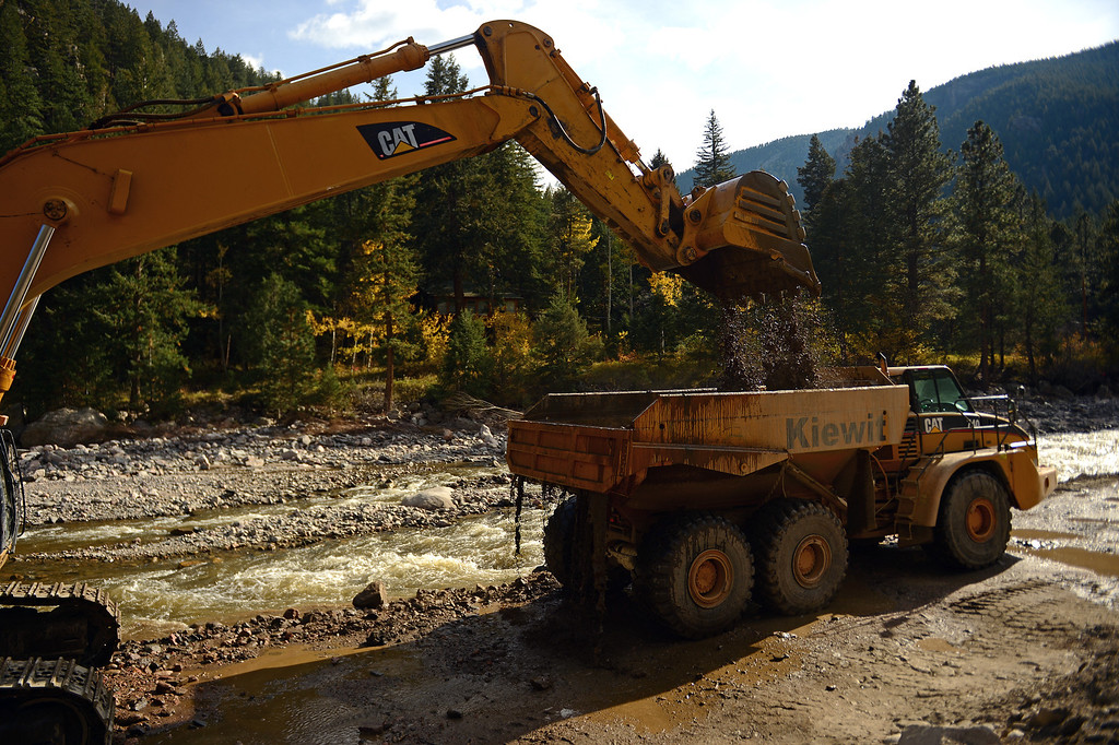 . An excavator puts rock and dirt  from the Big Thompson River into a dump truck near  Drake, Co on October 16, 2013. They are trying to re-divert the river back to where it used to flow. For nearly three weeks now, the Colorado Department of Transportation and it\'s contractor Kiewit Infrastructure Co has been working on US 34 from both the Estes Park and Loveland sides to provide a temporary roadway by December 1, 2013. (Photo By Helen H. Richardson/ The Denver Post)