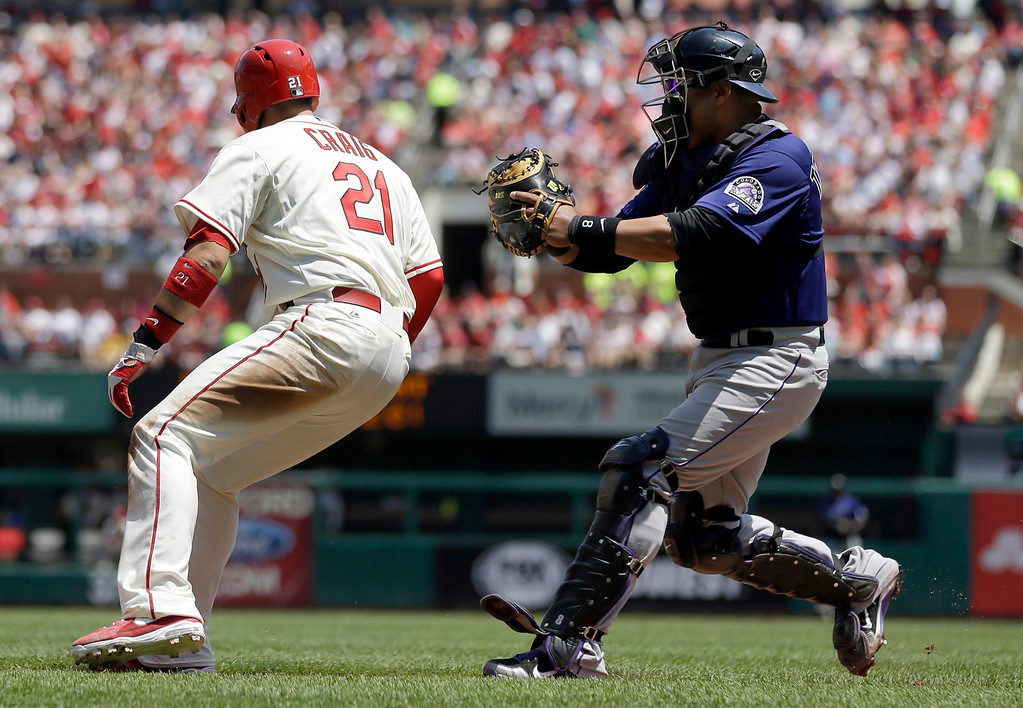 . St. Louis Cardinals\' Allen Craig, left, is tagged out by Colorado Rockies catcher Yorvit Torrealba after being caught between third and home during the second inning of a baseball game Saturday, May 11, 2013, in St. Louis. (AP Photo/Jeff Roberson)