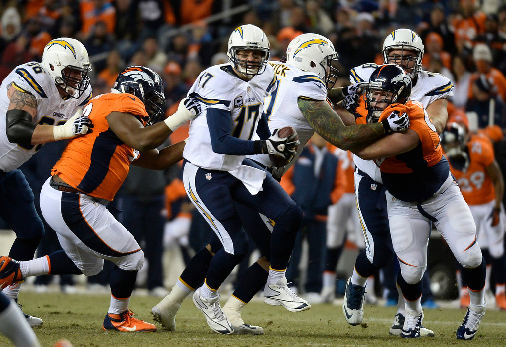 . Denver Broncos defensive tackle Sylvester Williams (92) gets a hold of San Diego Chargers quarterback Philip Rivers (17) for a sack during the first quarter. The Denver Broncos vs. the San Diego Chargers at Sports Authority Field at Mile High in Denver on December 12, 2013. (Photo by John Leyba/The Denver Post)