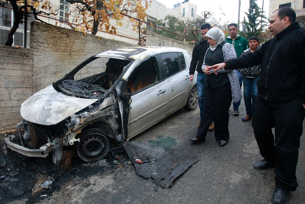 . Palestinian Dr. Laila Ghannam, the governor of Ramallah and al-Bireh, inspects an area attacked by suspected Jewish settlers in the Jalazoun refugee camp north of Ramallah, Tuesday, Dec. 31, 2013.  Israeli police say suspected Jewish vandals set fire to three vehicles in the West Bank early Tuesday and sprayed threatening graffiti referencing U.S. Secretary of State John Kerry ahead of his expected visit to the region this week. (AP Photo/Majdi Mohammed)