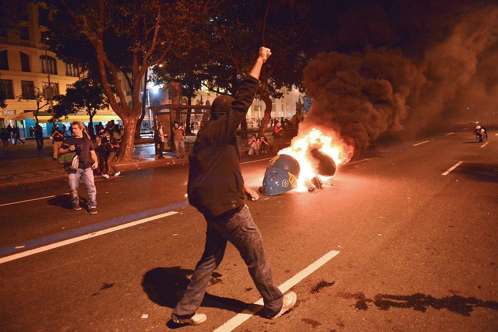 """. Demonstrators light a fire during the \""""Teachers\' day\"""" protest in demand of better working conditions and against police violence, on October 15, 2013 in Rio de Janeiro, Brazil. AFP PHOTO / CHRISTOPHE SIMON/AFP/Getty Images"""