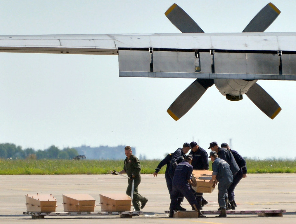 . Ukrainian servicemen carry a coffin that contains the body from downed Malaysia Airlines flight MH17 during a sombre ceremony in Kharkiv on July 23, 2014. The first plane carrying bodies from downed Malaysia Airlines flight MH17 on July 23 left eastern Ukraine for the Netherlands. The Dutch military aircraft took off from the airport in the government-controlled city of Kharkiv bound for Eindhoven after the first group of victims\' remains were loaded onto the plane in wooden coffins. AFP PHOTO/ GENYA  SAVILOV/AFP/Getty Images
