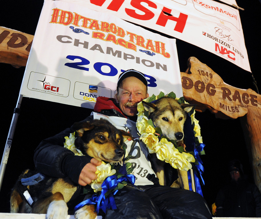 . Mitch Seavey became the oldest winner and a two-time Iditarod champion when he drove his dog team under the burled arch in Nome on Tuesday evening, March 12, 2013. He sits with his two lead dogs, Tanner, left and Taurus, right. (AP Photo/The Anchorage Daily News, Bill Roth)