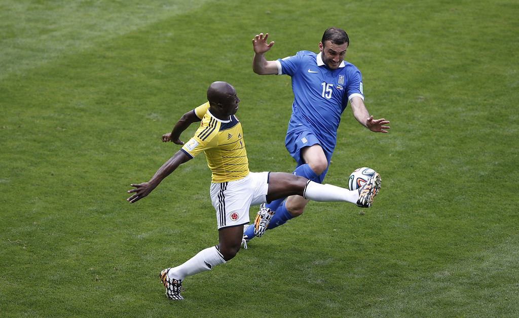 . Greece\'s defender Vasilis Torosidis (R) vies with Colombia\'s defender Pablo Armero (L) during a Group C football match between Colombia and Greece at the Mineirao Arena in Belo Horizonte during the 2014 FIFA World Cup on June 14, 2014.   AFP PHOTO / ADRIAN DENNIS