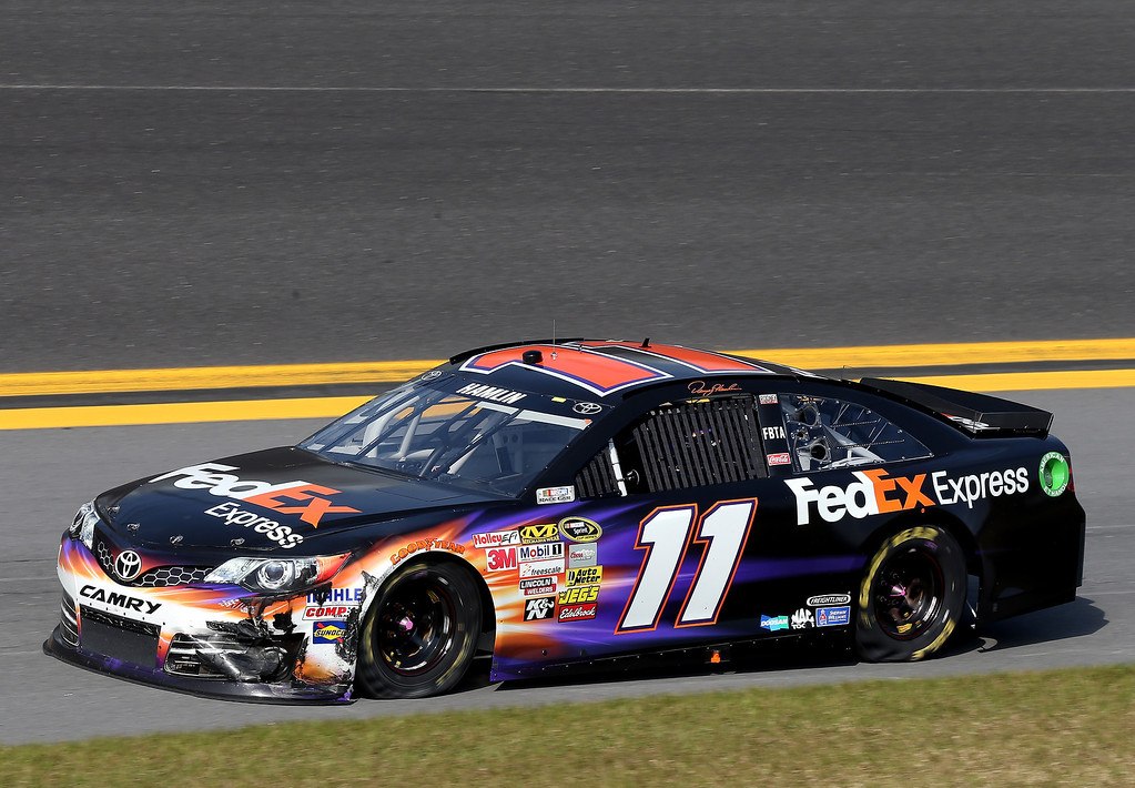 . Denny Hamlin, driver of the #11 FedEx Express Toyota, drives down the aprin after an incident in the NASCAR Sprint Cup Series Budweiser Duel 1 at Daytona International Speedway on February 21, 2013 in Daytona Beach, Florida.  (Photo by Matthew Stockman/Getty Images)
