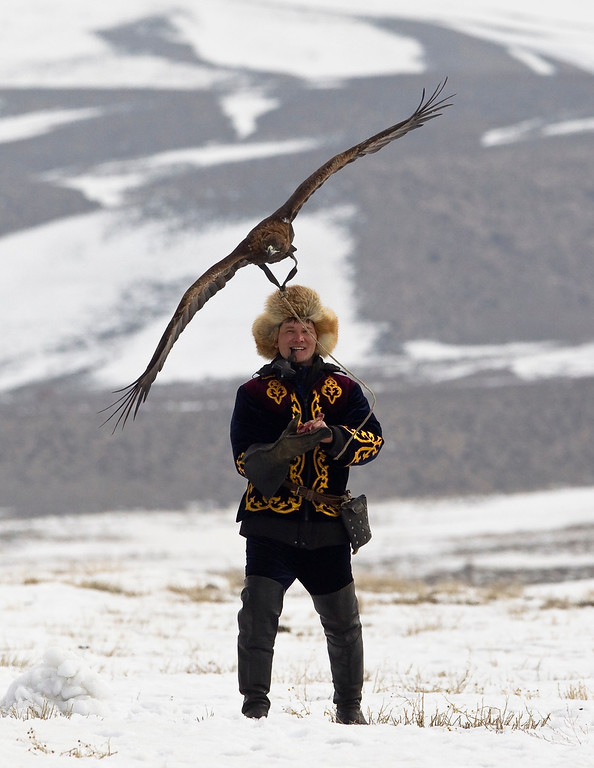 . A Kazakh hunter watches as his tamed golden eagle flies during an annual hunting competition in Chengelsy Gorge, some 150 km (93 miles) east of Almaty February 22, 2013. Picture taken February 22, 2013.  REUTERS/Shamil Zhumatov