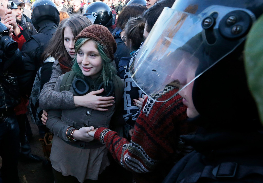. Gay rights activists are surrounded by police and anti-gay protesters during a gay rights rally in St. Petersburg, Russia, Saturday, Oct. 12, 2013. A gay rights rally in St. Petersburg has ended in scuffles after several dozen protesters were confronted by about 200 conservative and religious activists. The police standing nearby waited until clashes broke out between the two groups before intervening. According to Russian news agencies, the police detained 67 people from both sides. (AP Photo / Dmitry Lovetsky)