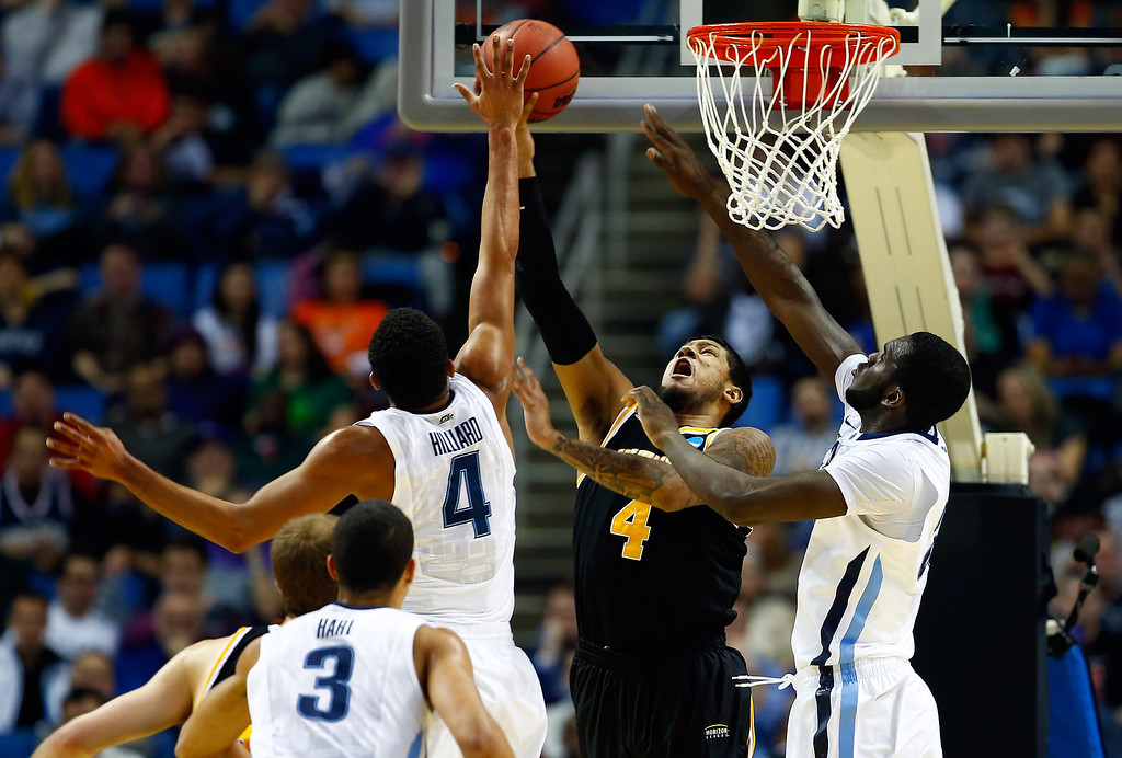 . BUFFALO, NY - MARCH 20: Darrun Hilliard II #4 of the Villanova Wildcats goes up for a shot as Malcolm Moore #4 of the Milwaukee Panthers defends during the second round of the 2014 NCAA Men\'s Basketball Tournament at the First Niagara Center on March 20, 2014 in Buffalo, New York.  (Photo by Jared Wickerham/Getty Images)