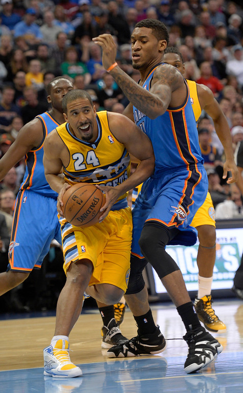 . Denver Nuggets point guard Andre Miller (24) drives on Oklahoma City Thunder small forward Perry Jones (3) during the second quarter December 17, 2013 at Pepsi Center. (Photo by John Leyba/The Denver Post)