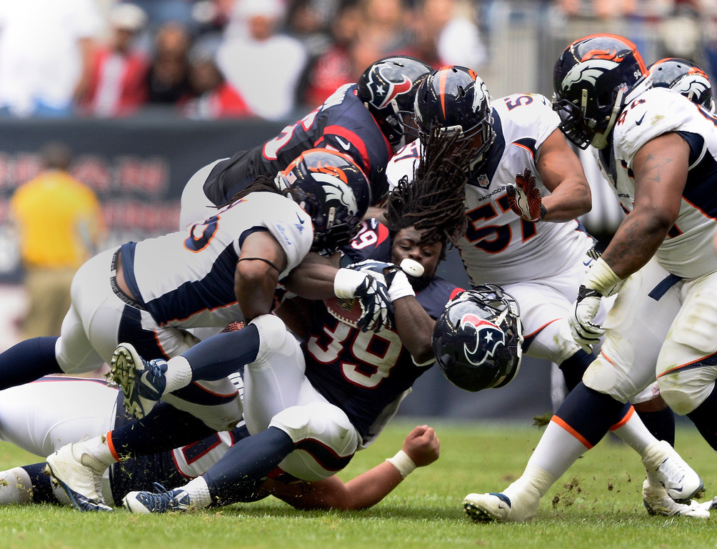 . HOUSTON, TX - DECEMBER 22: Houston Texans running back Deji Karim (39) gets his helmet knocked off by Denver Broncos defensive tackle Terrance Knighton (94) as Denver Broncos defensive end Jeremy Mincey (57) and Denver Broncos outside linebacker Nate Irving (56) come in to finish the tackle December 22, 2013 at Reliant Stadium. (Photo by John Leyba/The Denver Post)