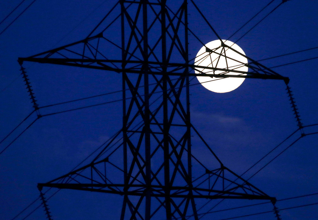 ". The moon rises behind power lines on Saturday, June 22, 2013, in Nashville, Tennessee. The biggest and brightest full moon of the year, called a ""super moon\"", happens as the moon passes closer to Earth than usual.  (AP Photo/Mark Humphrey)"