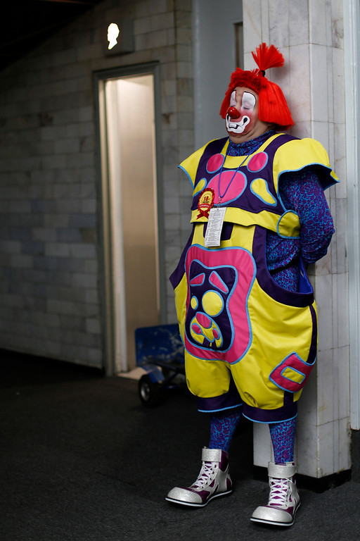. In this Monday, Oct. 21, 2013 photo, a clown relaxes briefly against a wall near the bathroom door on the first day of the 17th International Clown convention at a theater in Mexico City. Wearing oversized shoes, colorful wigs and red noses, the clowns lined up to register for the convention at a theater in Mexico\'s capital. (AP Photo/Dario Lopez-Mills)