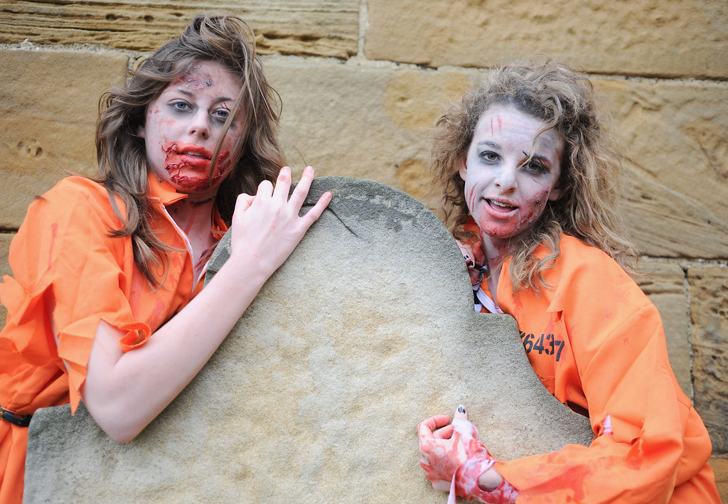 . WHITBY, ENGLAND - NOVEMBER 02: Two girls dressed as zombies pose for the camera at the Goth weekend on November 2, 2013 in Whitby, England. The Whitby Gothic Weekend that takes place in the Yorkshire seaside town twice yearly in Spring and Autumn started in 1994 and sees thousands of extravagantly dressed followers of Victoriana, Steampunk, Cybergoth and Romanticism visit to take part in celebrating Gothic culture.  (Photo by Ian Forsyth/Getty Images)