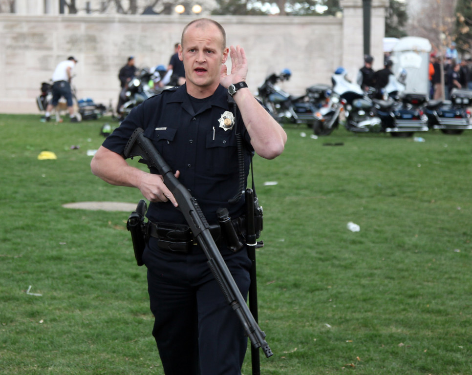 . Denver, CO. - April 20: A Denver Police officer directs people away from Civic Center Park as a shooting victim behind him is being treated after a 4/20 pot rally Saturday afternoon, April 20th, 2013. . Two people were shot during Saturday\'s annual 4/20 marijuana rally, held on a day cannabis enthusiasts regard as a holiday called 4/20 drew tens of thousands to Denver\'s Civic Center park. This is the first 4/20 marijuana rally since Colorado voters legalized marijuana use for people 21 and older in November. (Photo By Alex Scott/Special to The Denver Post)