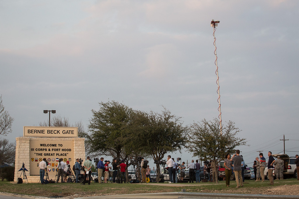 . Members of the media wait outside of the Bernie Beck Gate, an entrance to the Fort Hood military base, for updates on a shooting that occurred inside on Wednesday, April 2, 2014 in Fort Hood, Texas. (AP Photo/ Tamir Kalifa)