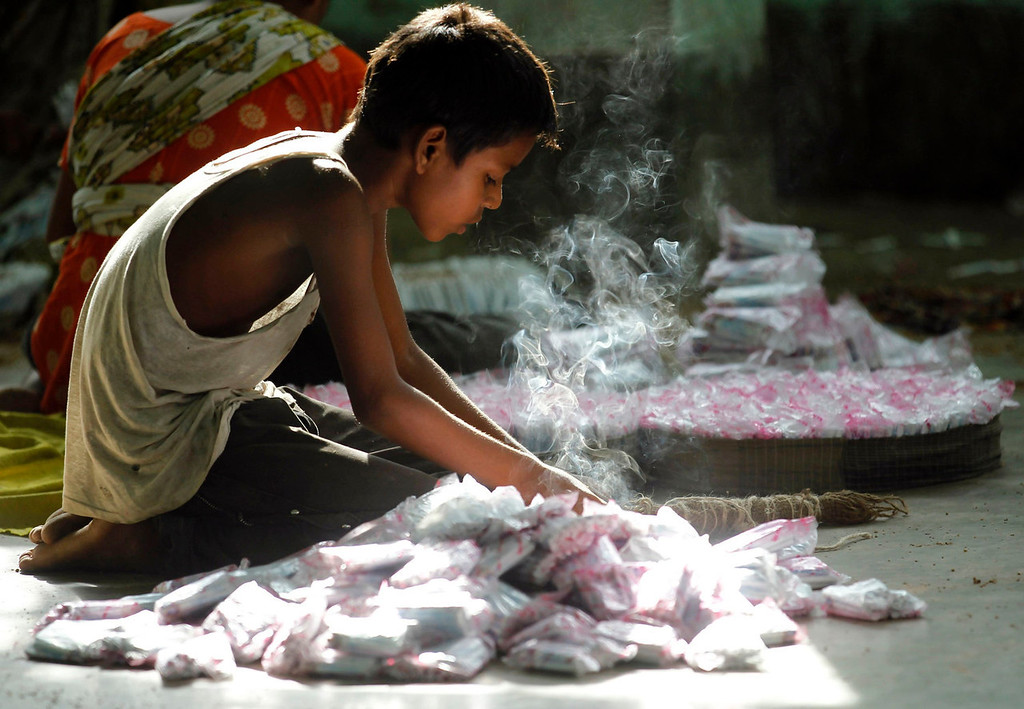 ". A child packs up cigarettes in a small bidi (cigarette) factory at Haragach in Rangpur district, Bangladesh July 13, 2013. According to a 2012 study by US-based NGO, Campaign for Tobacco-Free Kids, over 45,000 people in Bangladesh are employed in manufacturing inexpensive cigarettes known as bidis and this number includes ""many women and children working in household based establishments where they make low wages and live in poverty.\"" A 2011 research paper about bidi workers in Bangladesh, published in the journal Tobacco Control, says that working conditions can involve poor ventilation and exposure to tobacco dust, which can cause a range of health problems including respiratory and skin diseases. International attention has been focused on workers\' safety in Bangladesh since the disaster at Rana Plaza, a garment factory complex which collapsed in April, killing 1,132 workers.  REUTERS/Andrew Biraj"