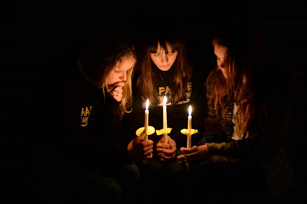 . CENTENNIAL, CO. - DECEMBER 20:  Arapahoe High School sophomores Sarah Dafoe, left, Ellie Maji, center, and Shanti Clark, right, held candles during a vigil for Claire Davis Friday night. Reverend Bradley Stoltenow led a candlelight vigil for Claire Davis at Shepherd of the Hills Lutheran Church December 20, 2013. Davis was injured inside the school last week. Photo By Karl Gehring/The Denver Post