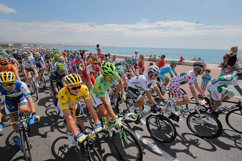 . The pack with Simon Gerrans of Australia, wearing the overall leader\'s yellow jersey, Peter Sagan of Slovakia, wearing the best sprinter\'s green jersey, Michal Kwiatkowski of Poland, wearing the best young rider\'s white jersey,and Pierre Roland of France, wearing the best climber\'s dotted jersey, rides along the mediterranean Sea at during the fifth stage of the Tour de France cycling race over 228.5 kilometers (142.8 miles) with start in Cagnes-sur-Mer and finish in Marseille, southern France, Wednesday July 3, 2013. (AP Photo/Christophe Ena)