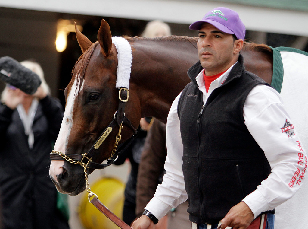 . Exercise rider William Delgado walks Kentucky Derby entrant California Chrome back to the barn after a morning workout at Churchill Downs Thursday, May 1, 2014, in Louisville, Ky. (AP Photo/Garry Jones)