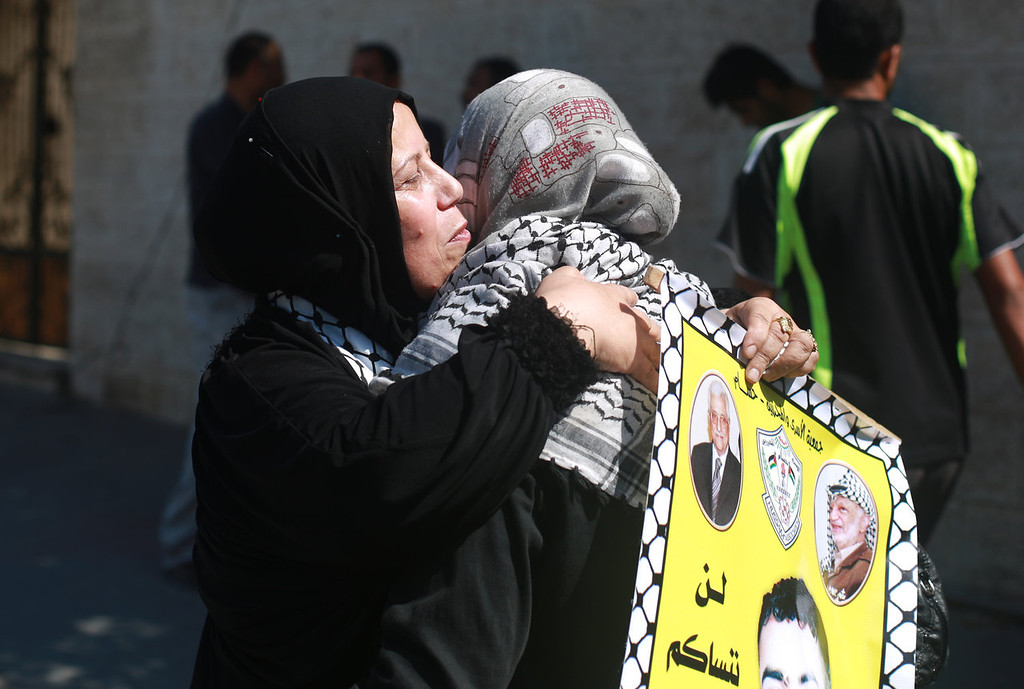 . Palestinian women hug each other after hearing that one of their relatives could be among the Palestinian prisoners held in Israeli jails to be released on July 29, 2013 outside the Red cross headquarters in Gaza city. In a tense session lasting more than five hours, ministers on July 28, 2013 endorsed Prime Minister Benjamin Netanyahu\'s proposal to release the 104 prisoners imprisoned before the 1993 Oslo peace accords as a gesture to the Palestinians.  MOHAMMED ABED/AFP/Getty Images