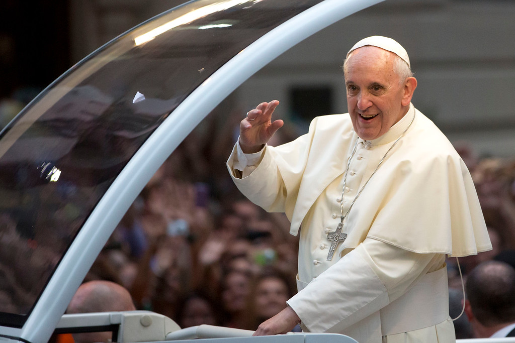 . Pope Francis waves from his popemobile as he makes his way into central Rio de Janeiro, Brazil, Monday, July 22, 2013. (AP Photo/Felipe Dana)