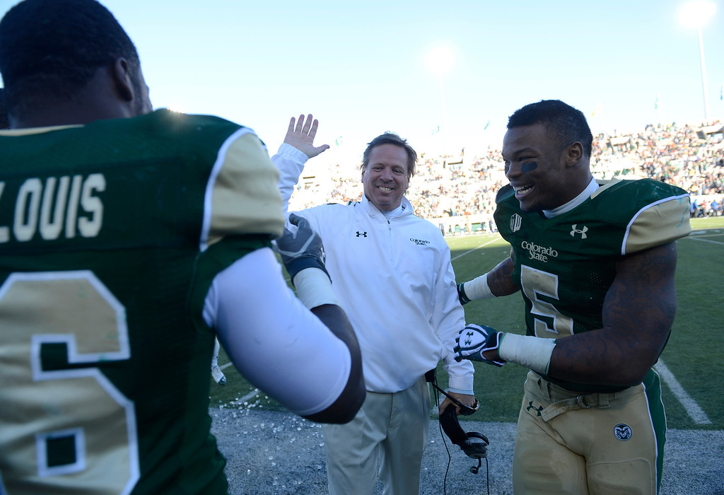 . Colorado State Rams football players, Kevin Pierre-Louis, left, and Kapri Bibbs, right, congratulate head coach, Jim McElwain, on the sidelines Saturday afternoon, November 30, 2013 moments before defeating Air Force 58-13. (Photo By Andy Cross/The Denver Post)
