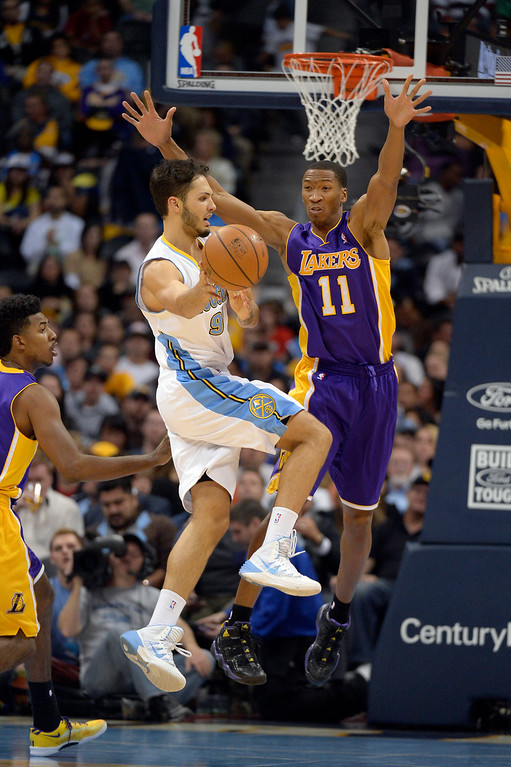. DENVER, CO - NOVEMBER 13: Denver Nuggets shooting guard Evan Fournier (94) passes off as Los Angeles Lakers shooting guard Wesley Johnson (11) defends on the play during the fourth quarter  November 13, 2013 at Pepsi Center. (Photo by John Leyba/The Denver Post)