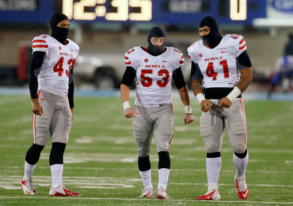 . From left, UNLV linebackers Tim Hasson, Max Ehlert and Tani Maka warm up before facing Air Force in the before the first quarter of an NCAA football game at Air Force Academy, Colo., on Thursday, Nov. 21, 2013. Temperatures are in the single digits with a light snow for the game. (AP Photo/David Zalubowski)