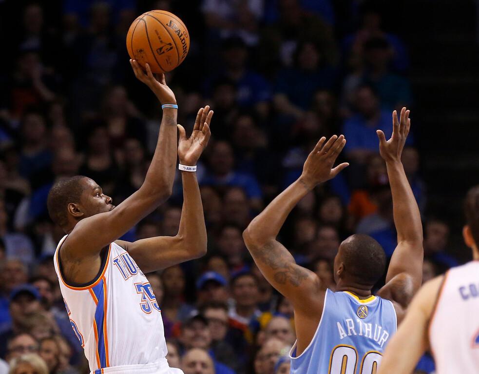 . Oklahoma City Thunder forward Kevin Durant (35) shoots over Denver Nuggets forward Darrell Arthur (00) in the first quarter of an NBA basketball game in Oklahoma City, Monday, March 24, 2014. (AP Photo/Sue Ogrocki)