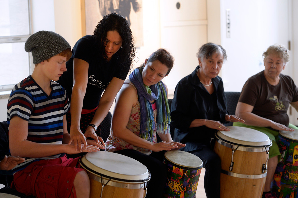. DENVER, CO - FEBRUARY 15: Tamil Maldonado , second from left, shows Smith Nagel, 14, proper drumming technique. Co-founders of Barrio E, Tamil Maldonado and husband Jose Daniel Beteta, gather students together at the McNichols Building in downtown Denver to teach a Bomba workshop. Bomba is an Afro-Caribbean rhythm with percussion, dance and song. Barrio E is a project based in Boulder that hopes to serve communities around Colorado and aims to expose, educate, and promote traditional Puerto Rican culture and music. Barrio E\'s next workshop for both kids and adults at McNichols will be Saturday, Mar. 15, 2014. (Photo by Kathryn Scott Osler/The Denver Post)